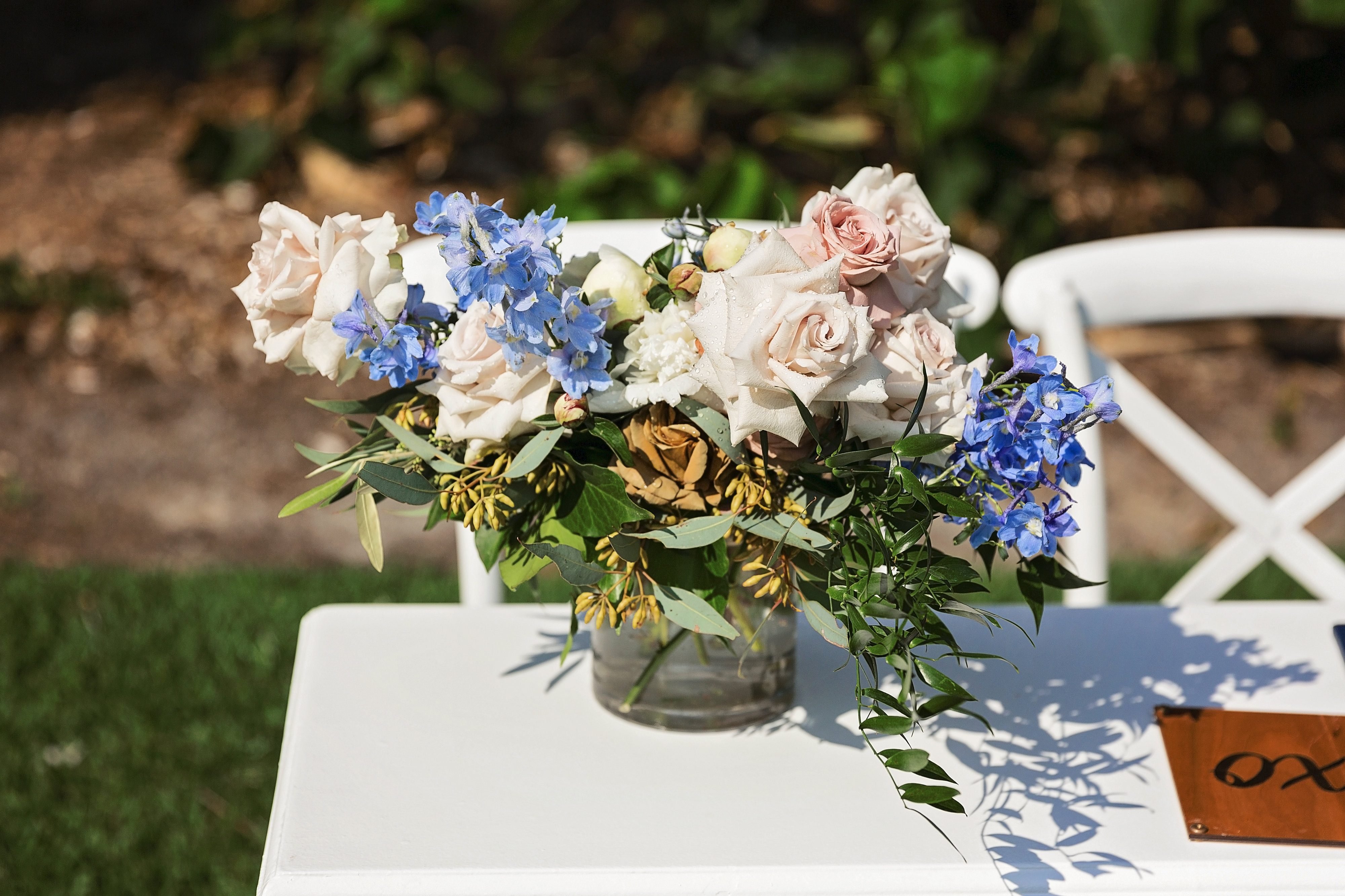 Coffee roses, blue delphinium, white phalaenopsis orchids and quicksand roses