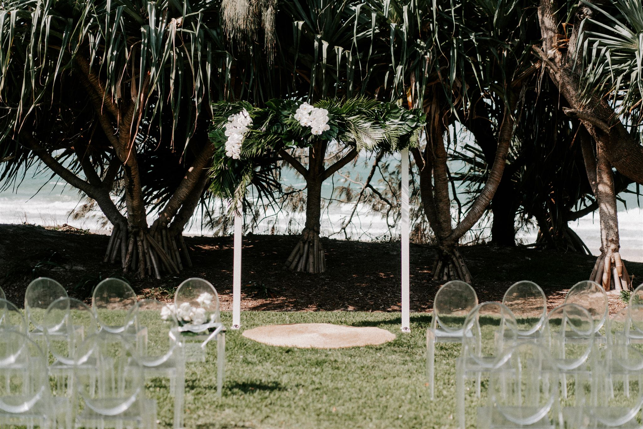 Ceremony arbour featuring tropical leaves and orchids