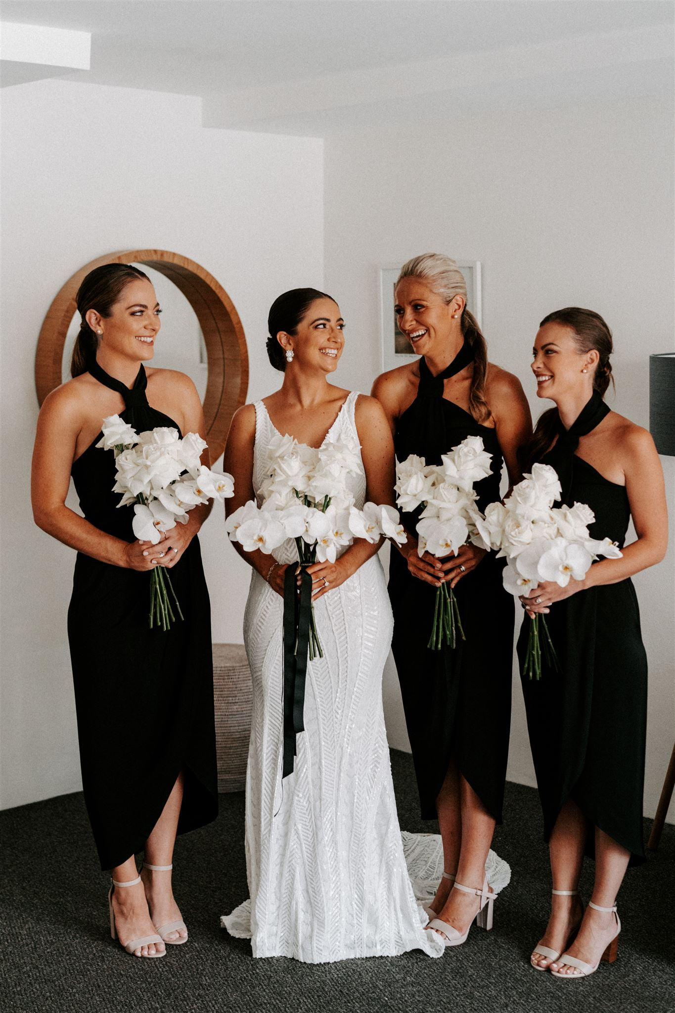 Modern white wedding bouquet featuring roses and orchids
