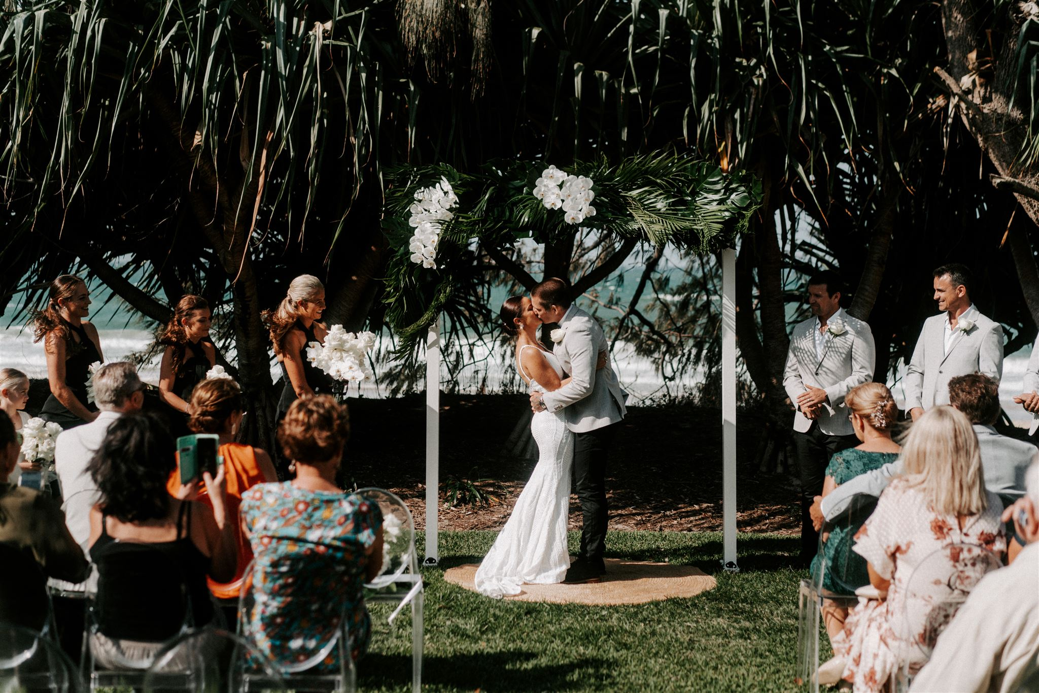Ceremony arbour design featuring tropical leaves and orchids