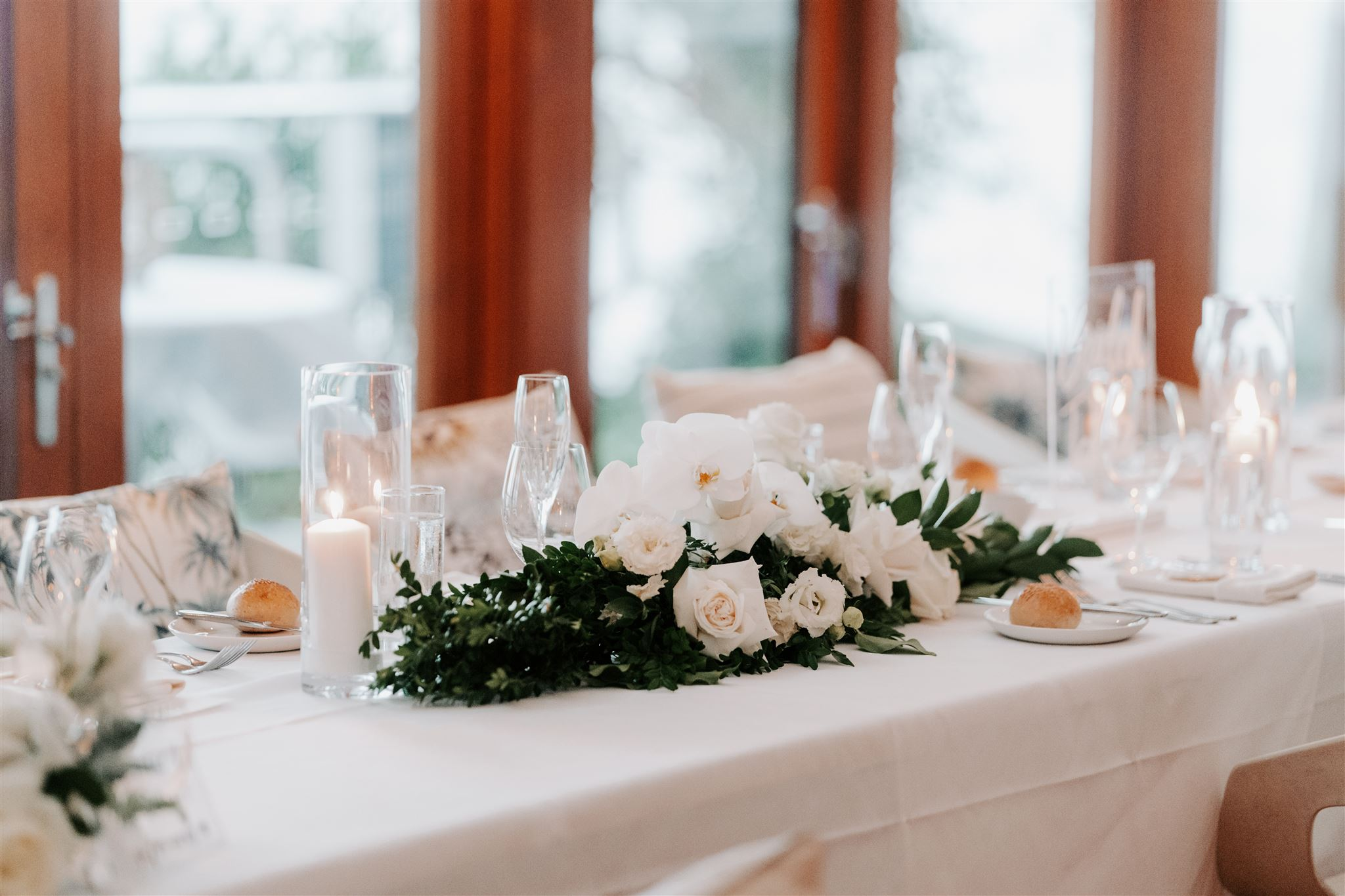 Reception table garland with tropical leaves and white blooms