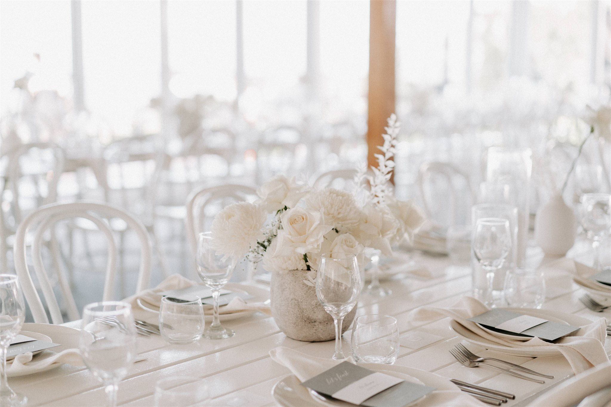 Modern reception table styling featuring textured vases and white blooms