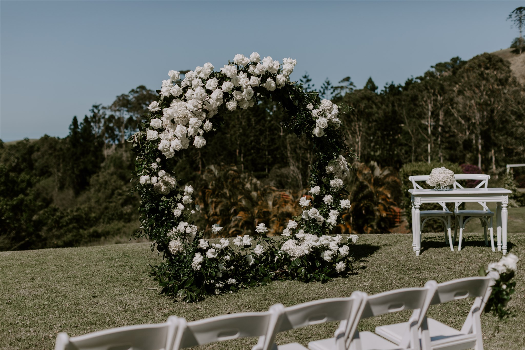 Ceremony love ring featuring white flowers and lush greenery