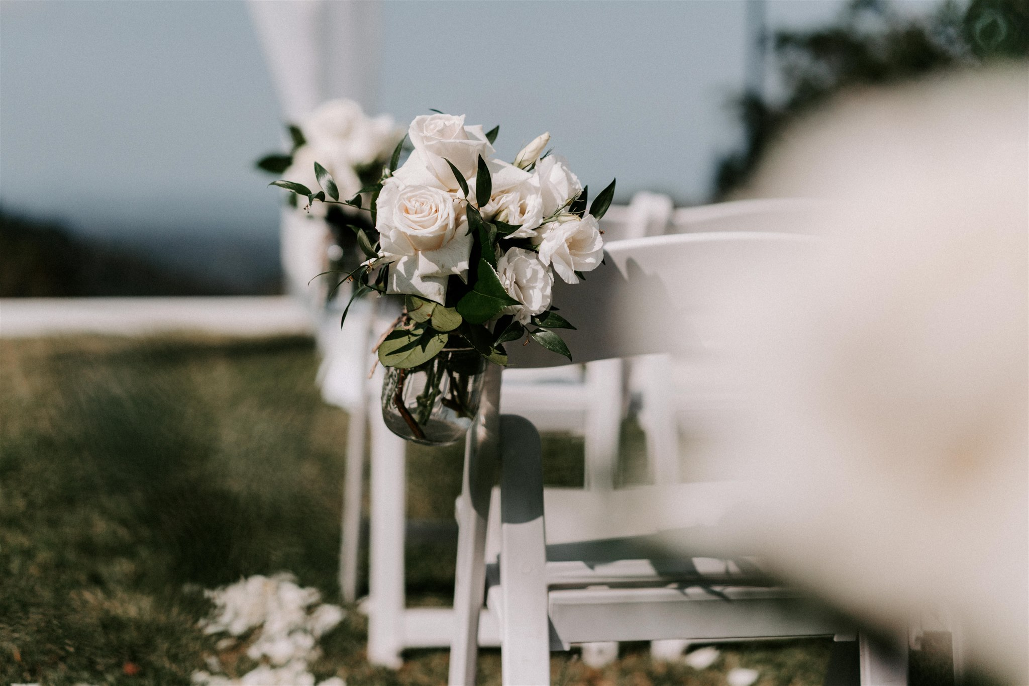 Ceremony chair jars featuring white blooms and greenery