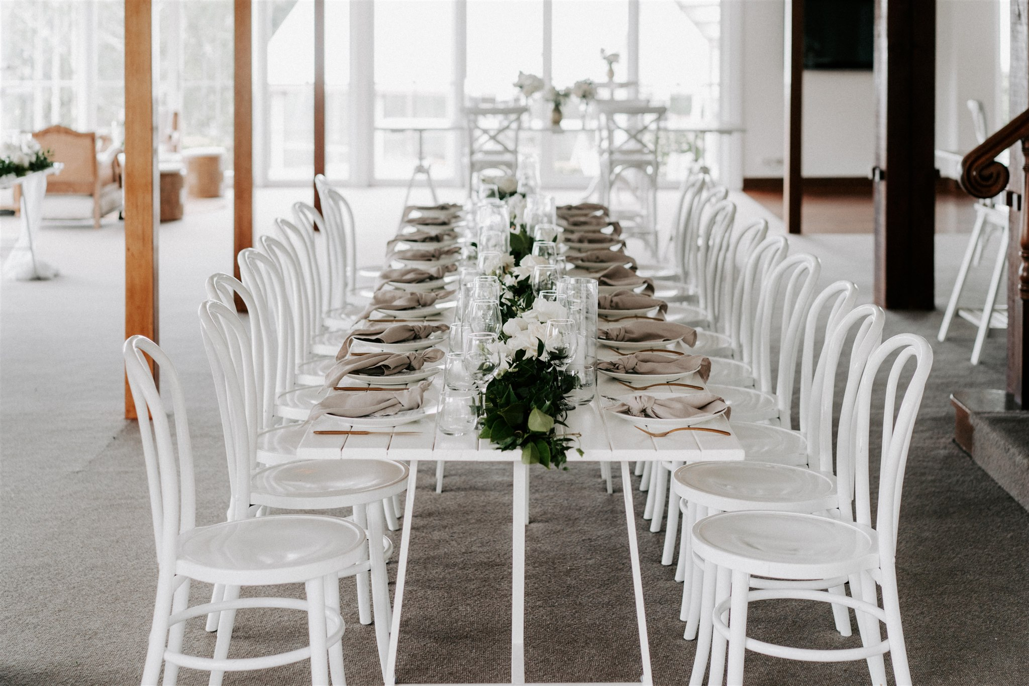 Reception table garlands featuring lush greenery and white blooms