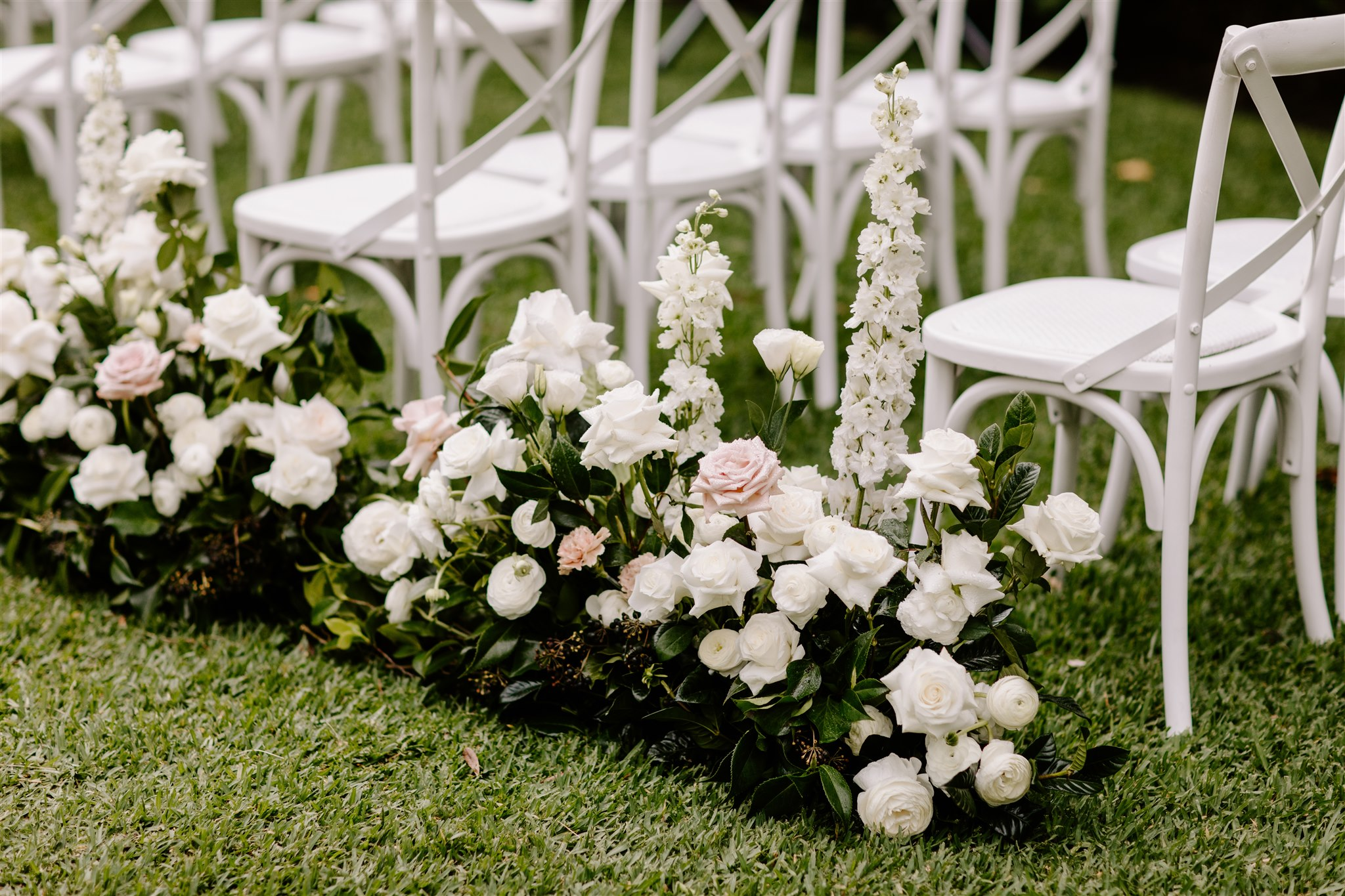 Ceremony aisle hedging featuring roses and ranunculus