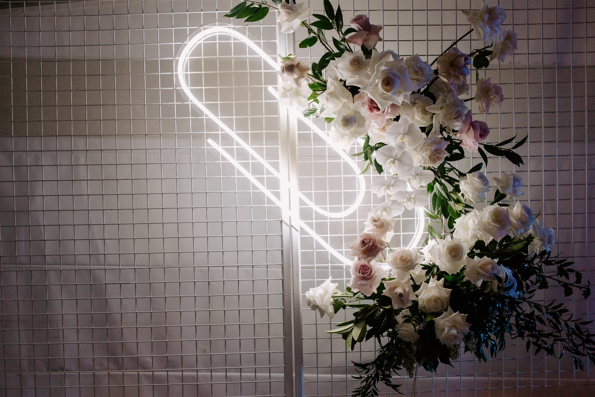 Neon sign floral feature with roses and orchids