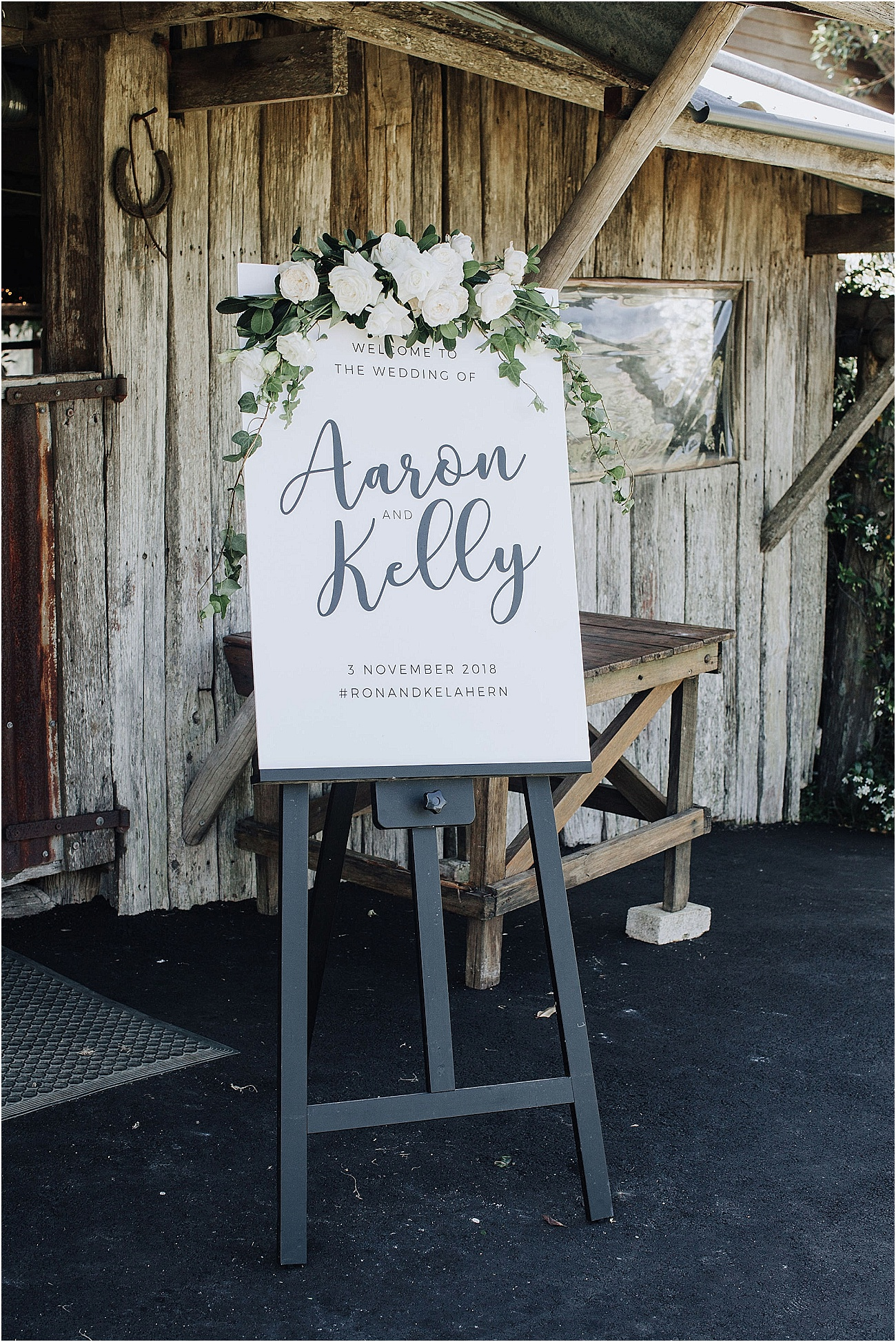Entry sign featuring white blooms and greenery