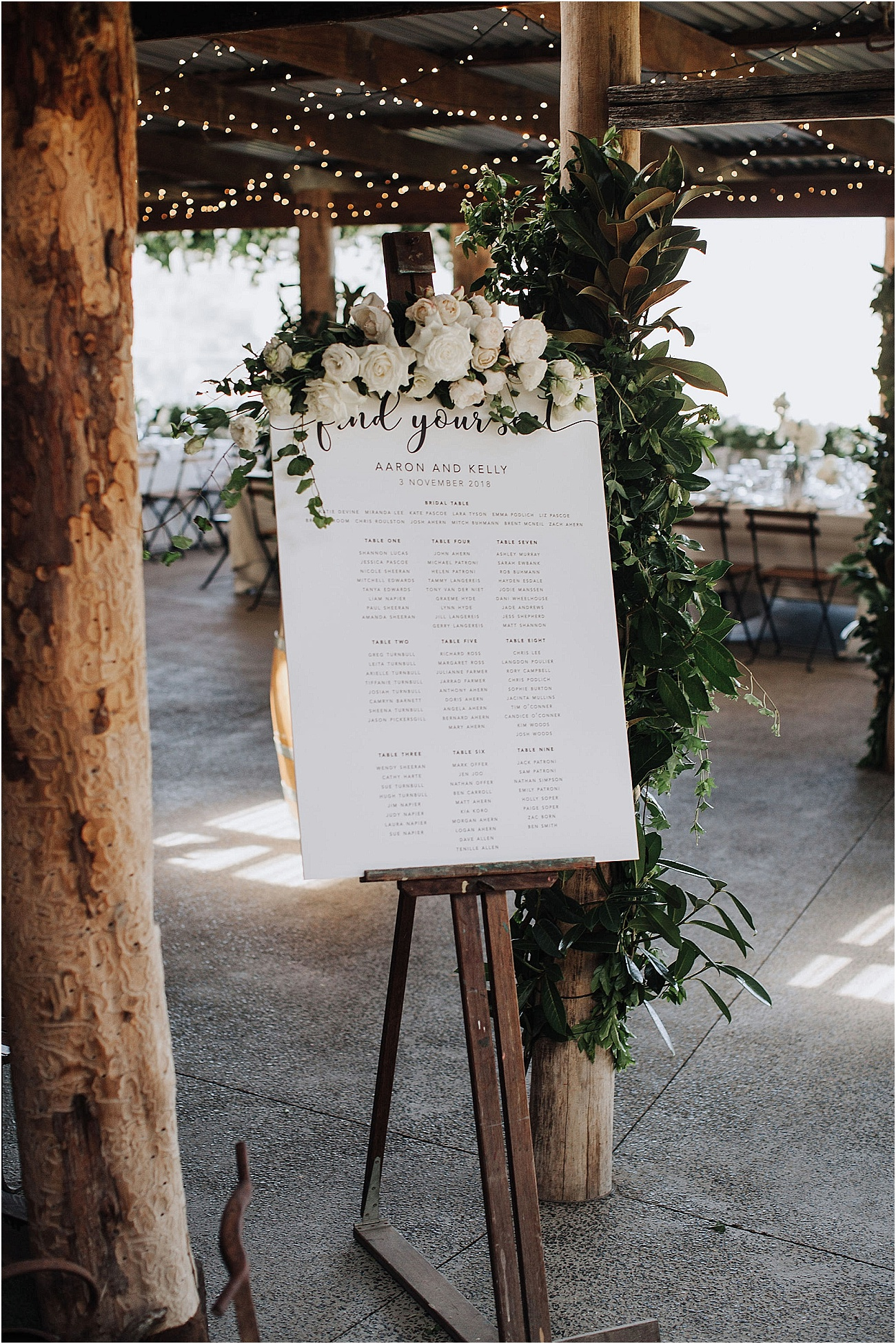 Seating board floral feature with white blooms and greenery