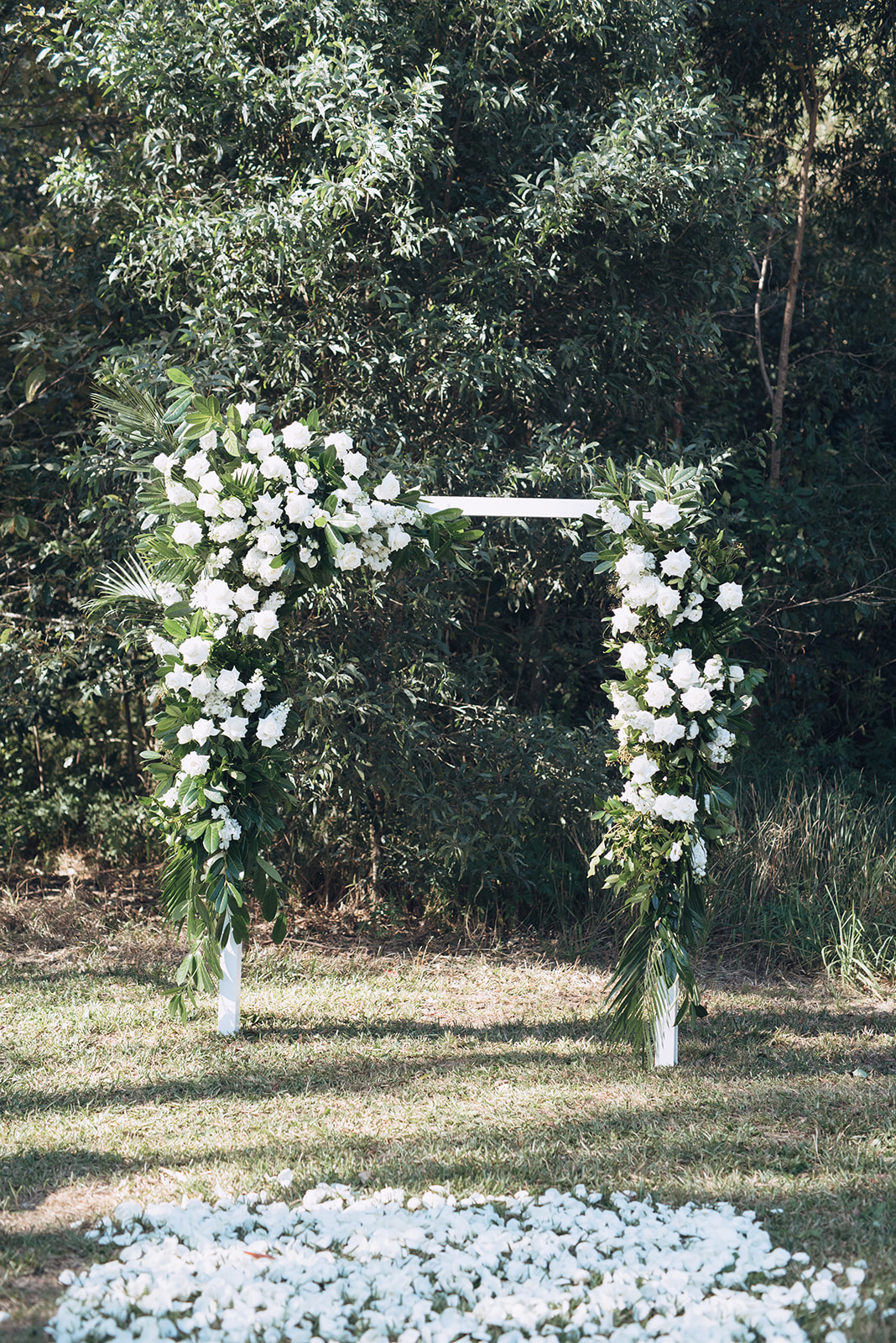 Modern white wedding arbour featuring lush greenery and white blooms