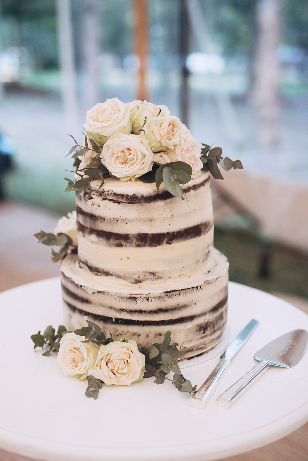 Wedding cake featuring blooms and greenery