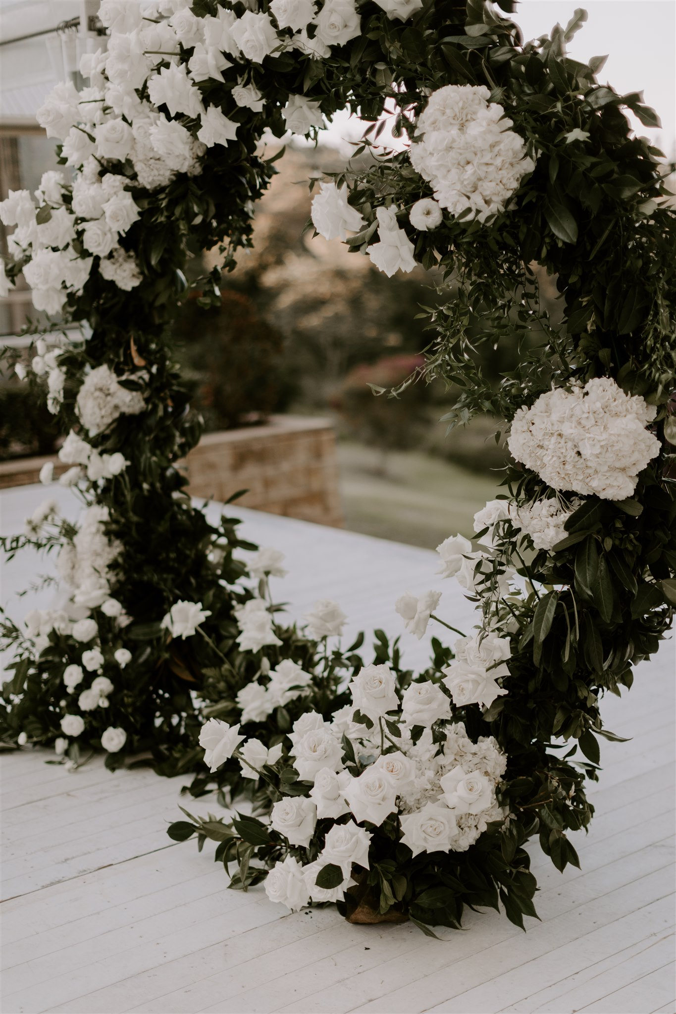 Love ring arbour with massed white blooms and lush greenery