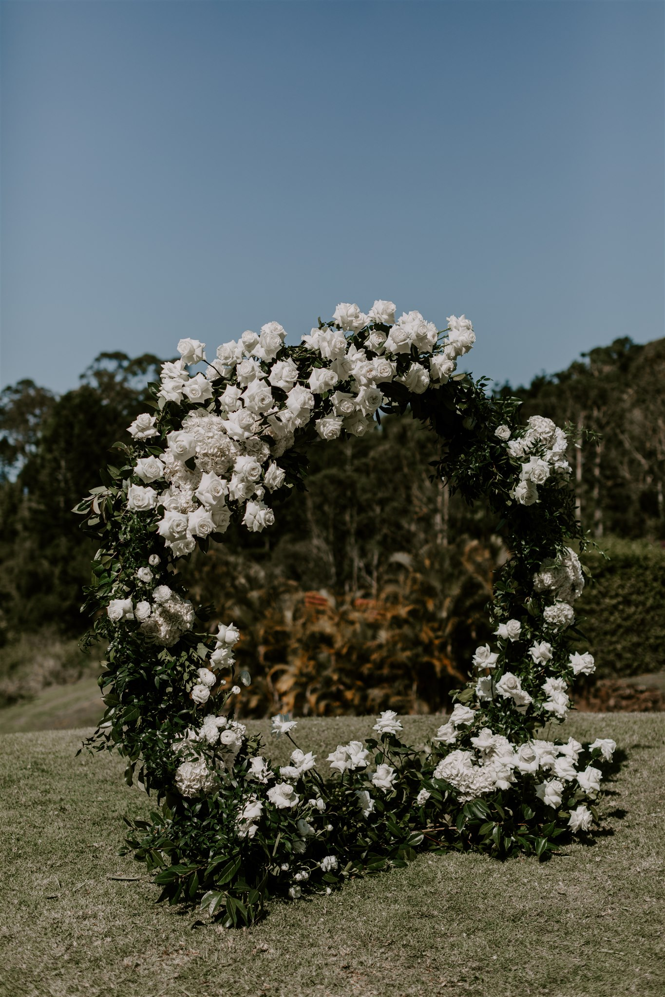 Love ring ceremony arbour with white blooms and lush greenery