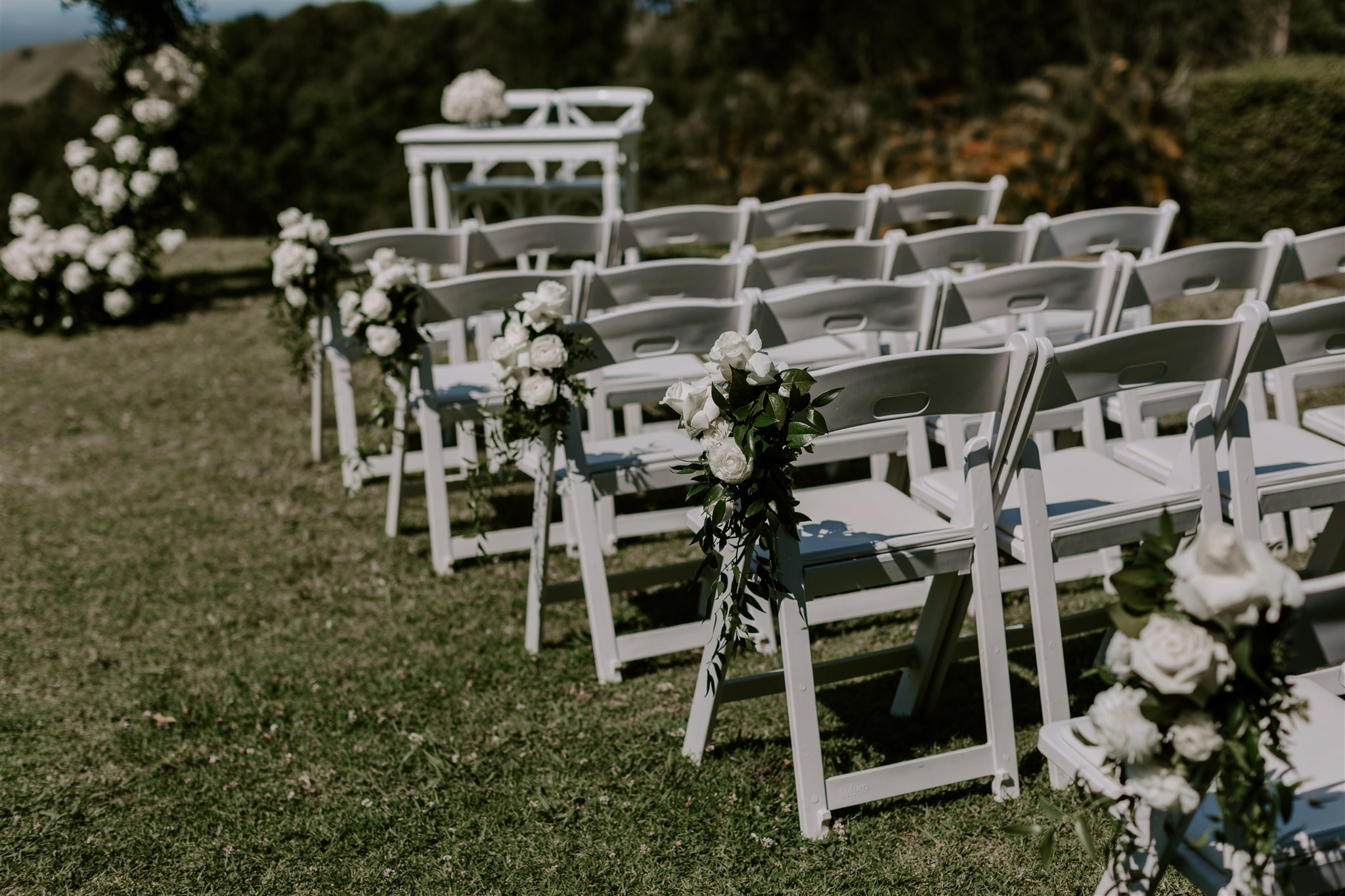 Ceremony chair aisle posies featuring white roses