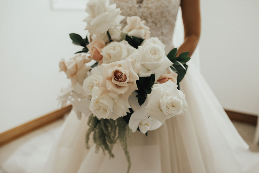 Modern bridal bouquet with pastel blooms and hints of tropical leaves