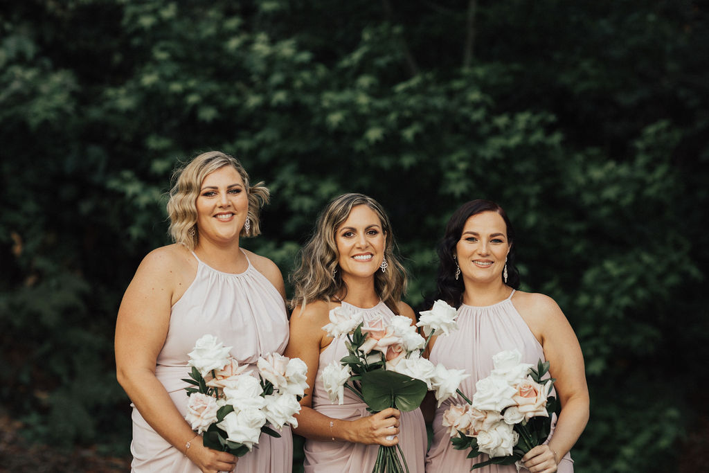 Bridesmaids bouquets featuring roses and tropical leaves