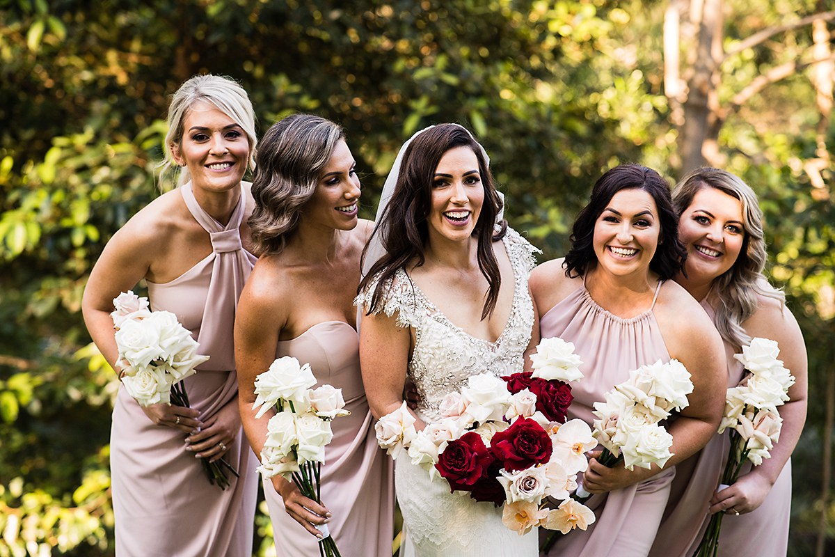 Red roses, peach orchids and pink roses in wedding bouquet