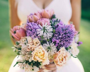 Hand held unstructured posy featuring peony tulips, double tulips, sea holly, liatris,