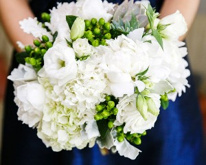 Clustered posy design of lisianthus, hydrangea, peonies, succulents and berry feature.