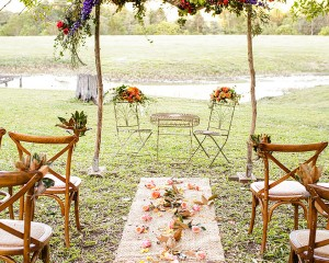 Rustic ceremony structure featuring lush floral swag and pathway heads, image by Calli B Photography