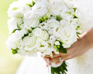 Hand held posy bouquet featuring tulips, roses, freesias, roses and lisianthus, with a hint of green.