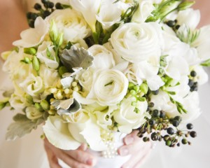 Unstructured posy of ranunculas, double tulips, freesias, roses and berry accents.