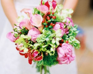 Unstructured bouquet of peonies, gloriosa lilies, calla lilies, mollucca balm, Singapore orchids and green tricks with feature berry - Image by Jodi McDonald