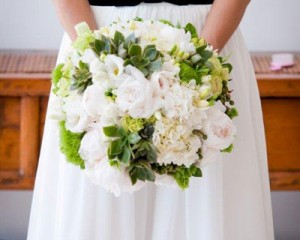 Unstructured bouquet featuring peonies, hydrangea, green tricks, succulents, freesias, Bells of Ireland, berry feature - Image by Davel Photography