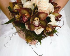 Unstructured posy bouquet of chocolate cymbidium orchids, Emmanuelle and Honeymoon roses, magnolia foliage and vine - Image by Calli B Photography