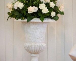 Altar pedestal design of roses, lisianthus and lush foliages