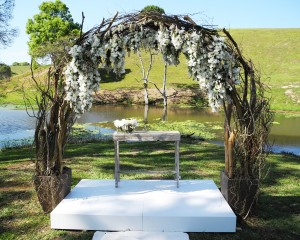 Rustic branch archway with suspended blooms featuring Andromeda and sweet pea.