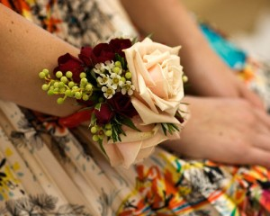 Wrist corsage featuring cream Sahara roses, dark red miniature roses with a touch of Rosemary, green berry and Geraldton Wax flower