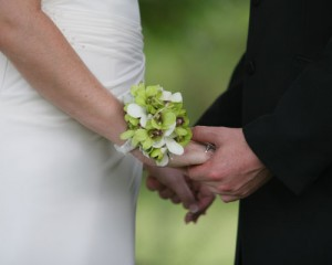 Bridal wrist corsage featuring white and green Singapore Orchids