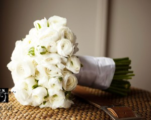 Hand held posy of white ranunculas.
