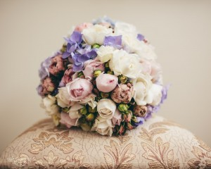 Hand held posy of David Austin roses, peonies and hydrangea