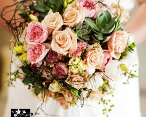 Unstructured posy design of Sahara and David Austin roses, lisianthus, succulents and berry and vine feature.
